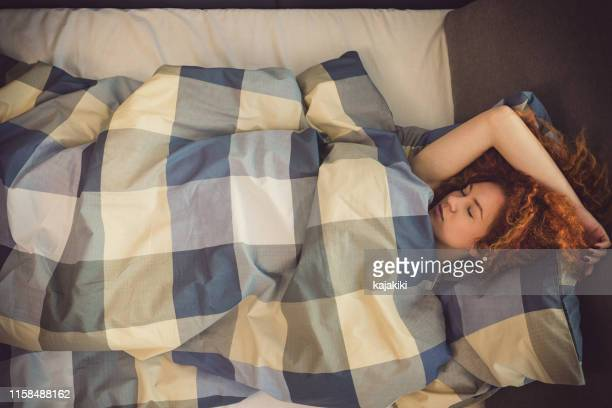 portrait of a beautiful young girl sleeping in bed - redhead stock pictures, royalty-free photos & images