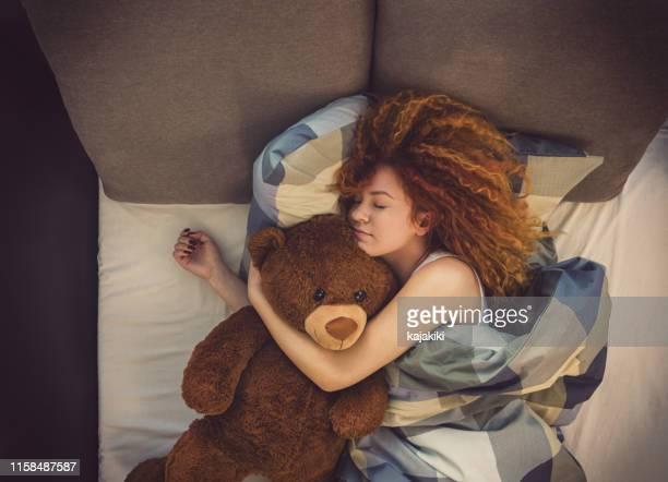 自宅でベッドで眠っているテディベアと美しい若い女の子の肖像画 - テディベア ストックフォトと画像