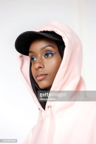 a portrait of a beautiful, young muslim woman wearing a black hijab, black baseball cap and a pink hoodie photographed in studio setting. - sombra maquiagem de olho - fotografias e filmes do acervo