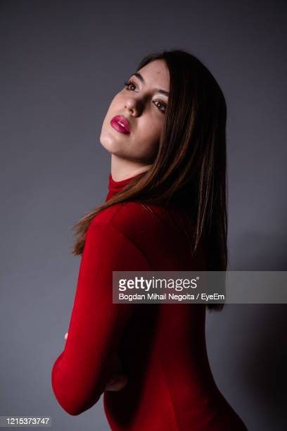 portrait of a beautiful young woman against gray background - bogdan negoita stock pictures, royalty-free photos & images