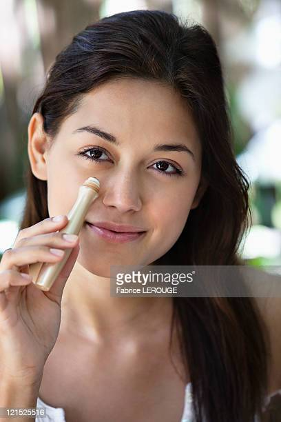 Portrait of a beautiful young woman applying make-up