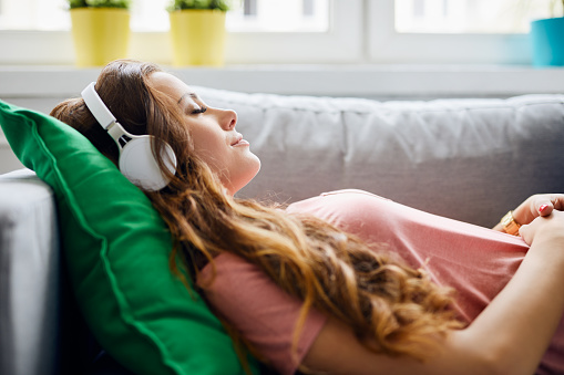 Portrait of a beautiful young woman lying on sofa with headphones on and closed eyes, relaxing 1008382428
