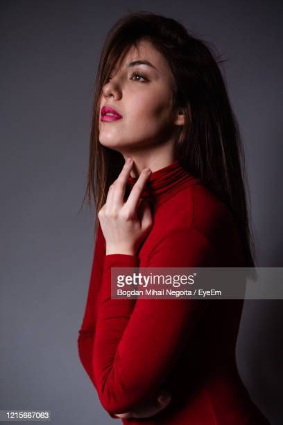 portrait of a beautiful young woman over black background - bogdan negoita stock pictures, royalty-free photos & images
