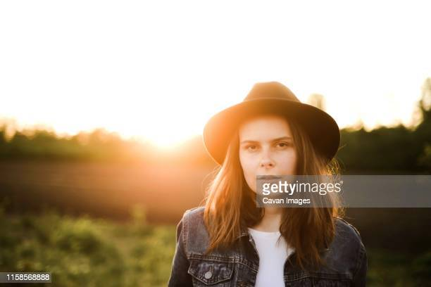 portrait of a beautiful young woman  standing against clear sky - golden hour stock pictures, royalty-free photos & images