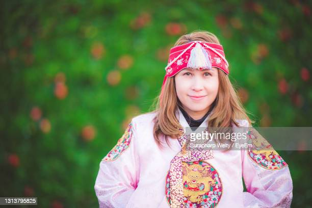 portrait of a beautiful young woman standing against pink background - south korea stock pictures, royalty-free photos & images