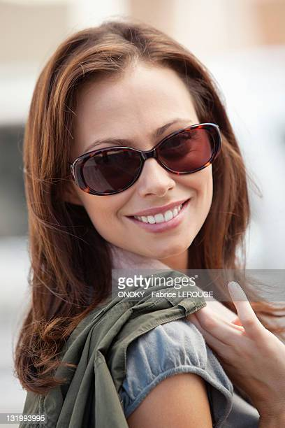portrait of a beautiful young woman wearing sunglasses - onoky stock-fotos und bilder