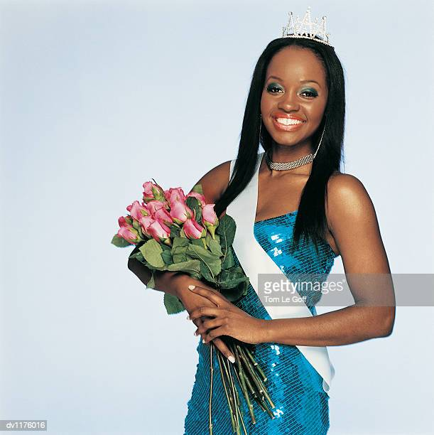 Portrait of a Beauty Queen Wearing a Sash and Holding a Bouquet of Red Roses