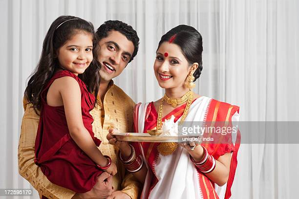 portrait of a bengali family with a plate of religious offerings - bengali girl stock photos and pictures