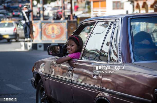 Portrait of a bhutanese girl smiling out of a car at the main central junction It´s a tourist attraction when a Police officer directs traffic with...