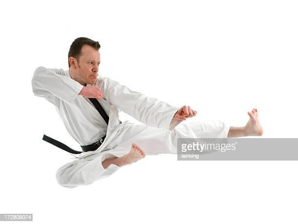 Portrait of a black belt man doing a high kick on white