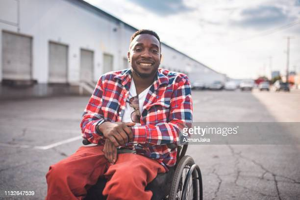 Portrait of a black disabled person in a wheelchair smiling and looking at camera