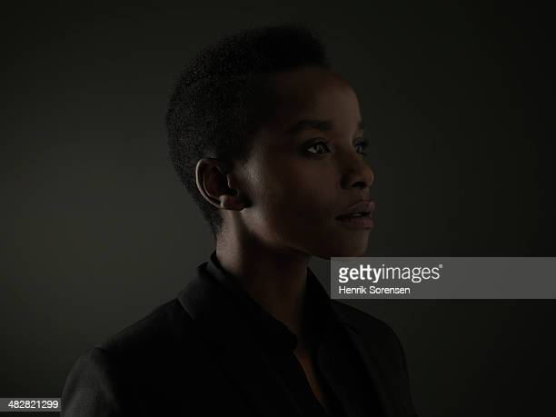 portrait of a black woman on a dark backdrop - only mid adult women stock pictures, royalty-free photos & images