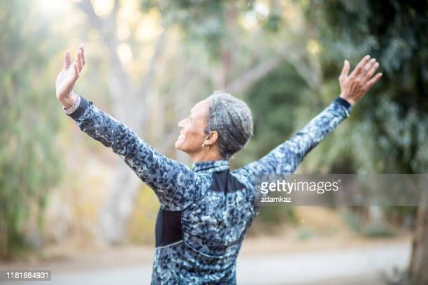 portrait of a black woman stretching - rear view stock pictures, royalty-free photos & images