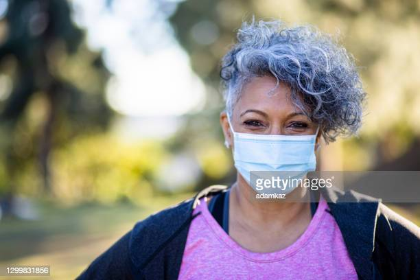 portrait of a black woman wearing a mask - adamkaz stock pictures, royalty-free photos & images