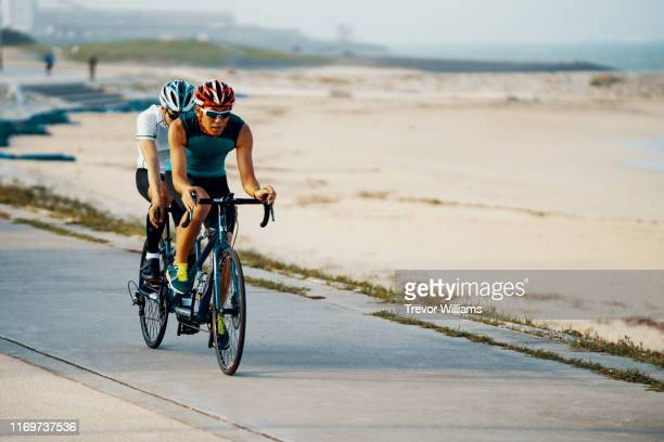portrait of a blind triathlete together with his guide and their tandem bicycle - disabilitycollection fotografías e imágenes de stock