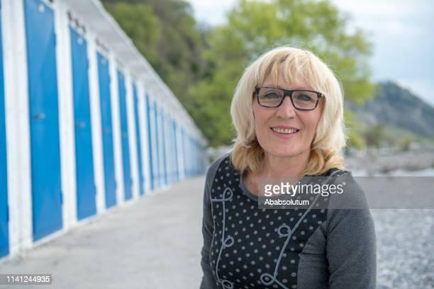 portrait of a blond senior caucasian woman at the seaside in spring, italy - melena mediana fotografías e imágenes de stock