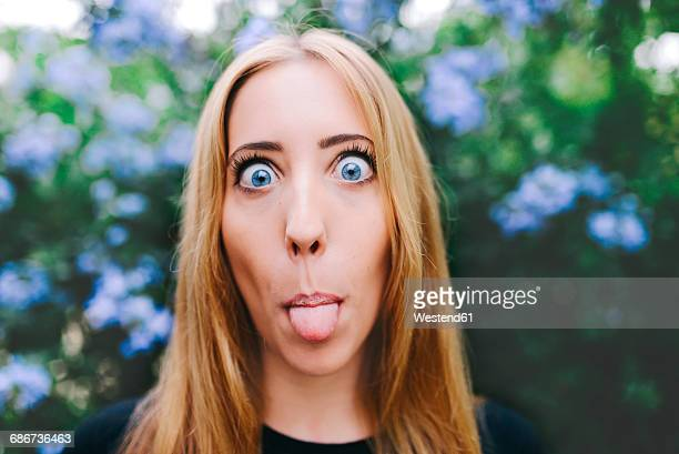 Portrait of a blond woman sticking out tongue