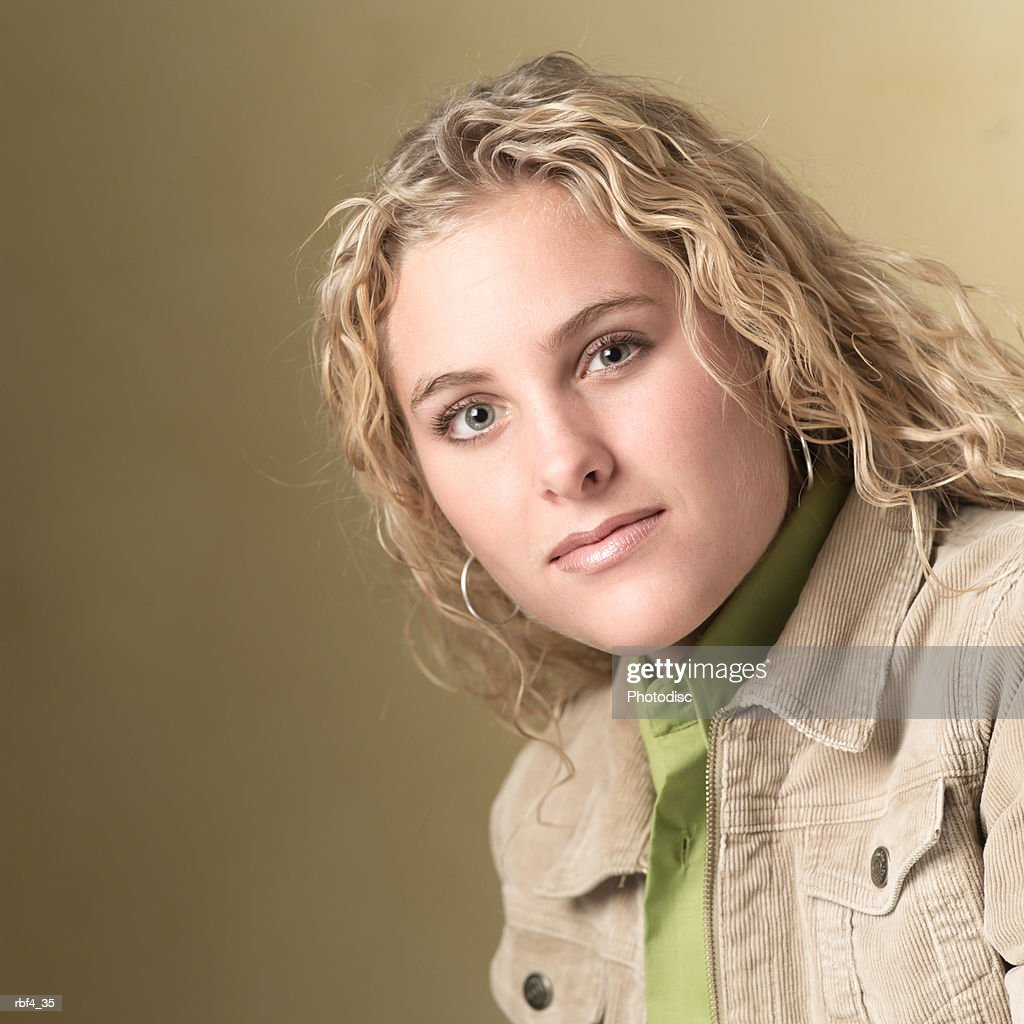 portrait of a blonde caucasian teenage girl in a green shirt and tan jacket as she smiles slightly : Stock Photo