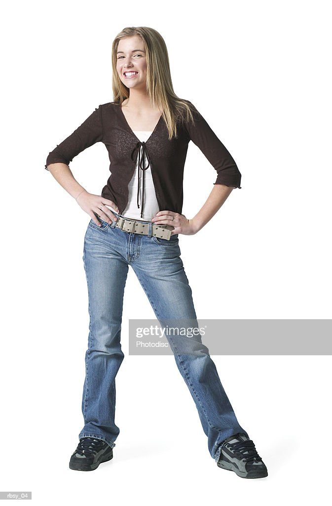 portrait of a blonde caucasian teenage girl in jeans and a purple shirt she looks forward smiling : Foto de stock