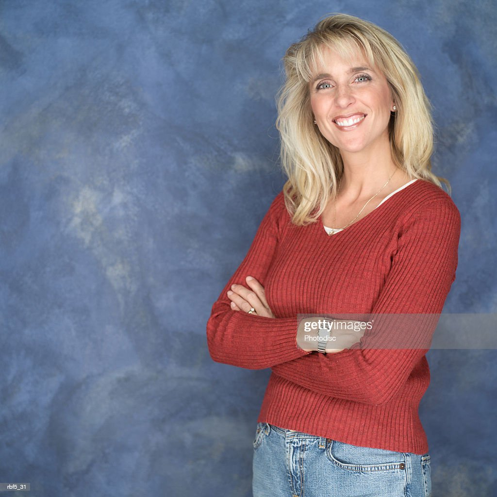 portrait of a blonde caucasian woman in a red sweater and jeans as she folds her arms and smiles : Stockfoto