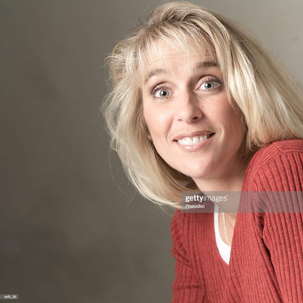 portrait of a blonde caucasian woman in a red sweater as she smiles into the camera : Bildbanksbilder