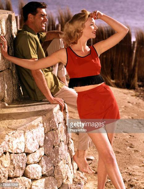 1962 A portrait of a blonde haired young woman wearing a red top with tassels and some red shorts whilst standing on a beach looking out to sea with...
