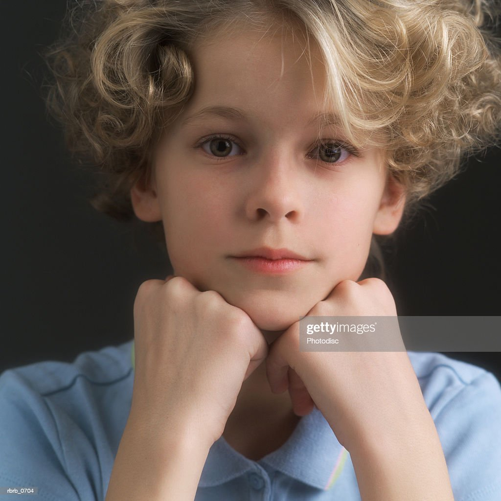 portrait of a blonde little girl as she rests her head on her hands and smiles slightly : Stockfoto