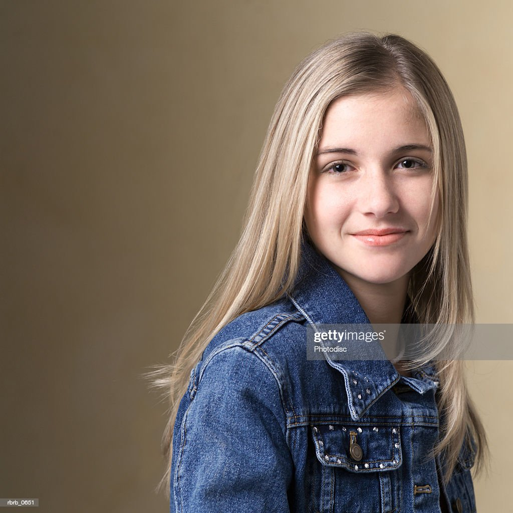 portrait of a blonde teenage girl in a jean jacket as she smiles : Stockfoto