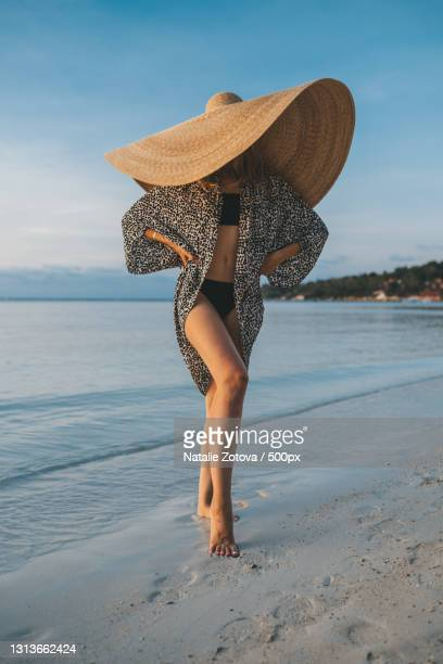 portrait of a blonde woman with an oversized straw hat on the beach - oversized stock pictures, royalty-free photos & images