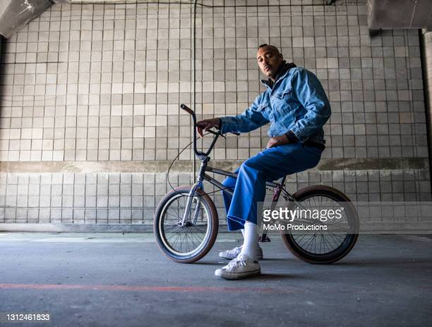 portrait of a bmx rider in warehouse environment - african american culture stock pictures, royalty-free photos & images