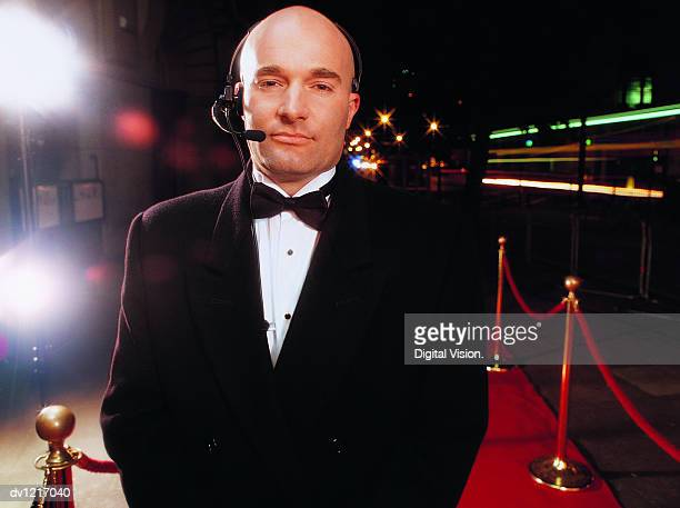 portrait of a bouncer wearing a headset standing on a red carpet at night - bouncer security staff stock photos and pictures