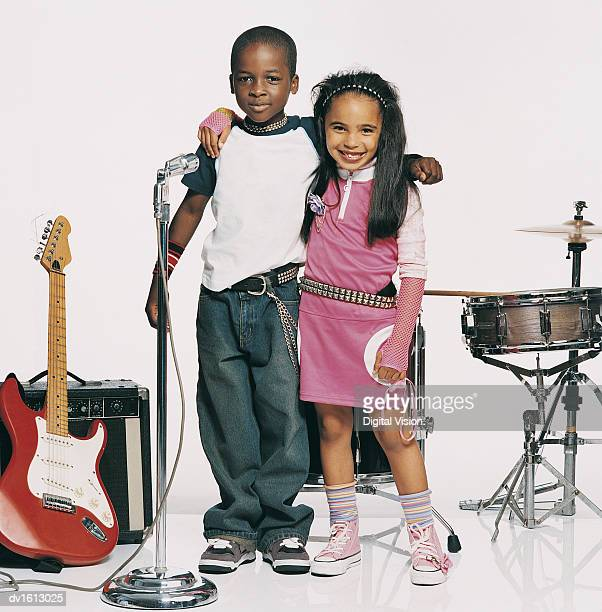 Portrait of a Boy And a Girl Dressed up as Pop Musicians Standing Between Instruments