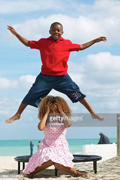 portrait of a boy (10-11) and girl (10-11) playing on a trampoline on a beach