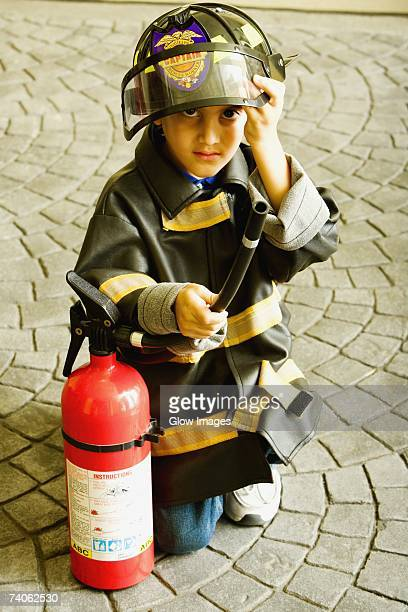 Portrait of a boy dressed as a firefighter and holding a fire extinguisher