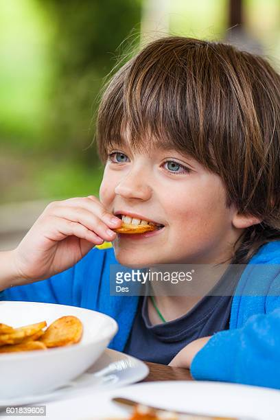 Portrait of a boy eating French fries