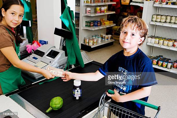 Portrait of a boy giving paper currency to a sales clerk