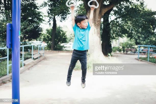 portrait of a boy hanging on playground equipment in the park - yusuke nishizawa bildbanksfoton och bilder