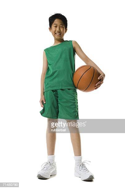Portrait of a boy holding a basketball and smiling