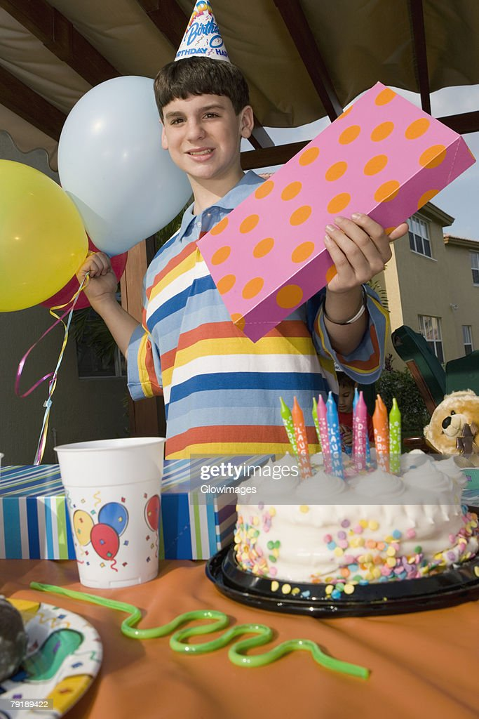 Portrait of a boy holding a birthday present and balloons : Stock Photo