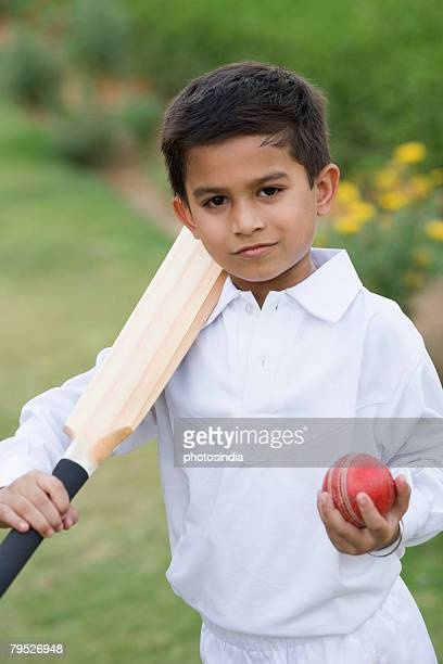 Portrait of a boy holding a cricket bat and a cricket ball