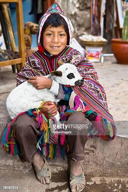 Portrait of a boy holding a lamb and smiling, Pisaq, Urubamba Valley, Peru