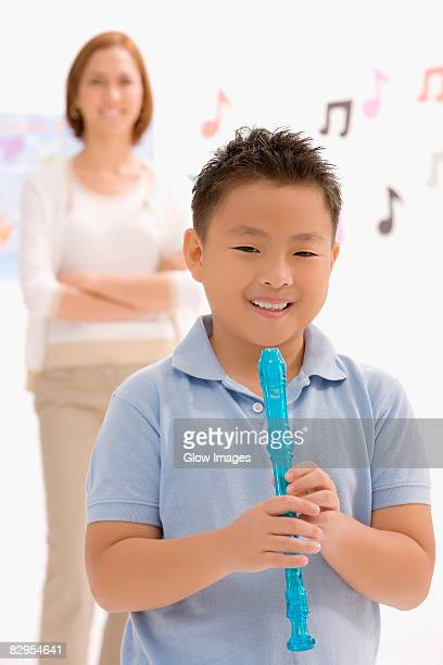 portrait of a boy holding a recorder flute and smiling - recorder musical instrument stock photos and pictures