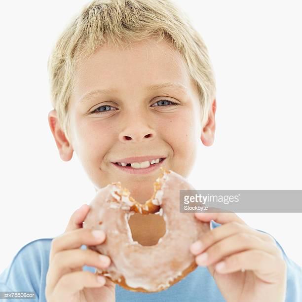 portrait of a boy (8-9) holding a sugar glazed doughnut