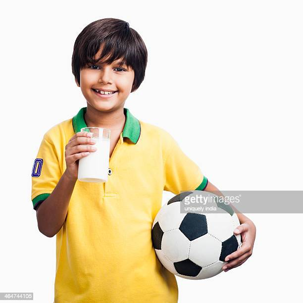 Portrait of a boy holding glass of milk and a soccer ball