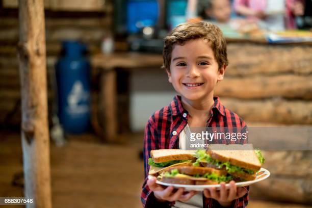 retrato de um menino segurando sanduíches em uma casa de campo e olhando feliz - só um menino - fotografias e filmes do acervo