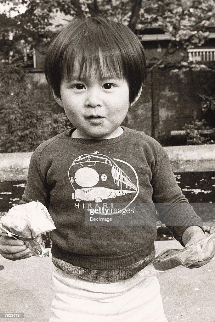 Portrait of a boy holding snacks : Stock Photo