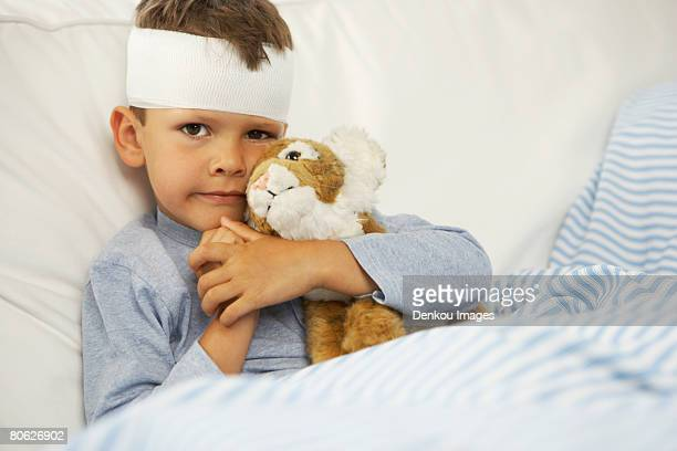 Portrait of a boy hugging a stuffed toy with a bandage on his forehead