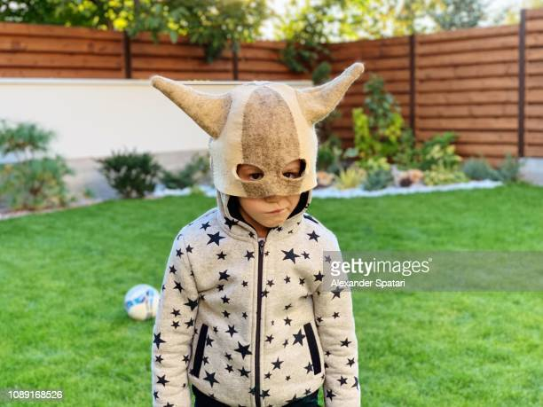 portrait of a boy in a funny horns mask at the back yard - costume stock pictures, royalty-free photos & images