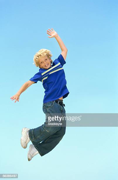 portrait of a boy jumping in mid-air