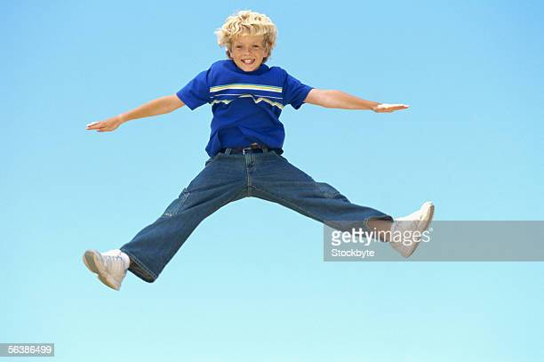 portrait of a boy jumping in mid-air - benen gespreid stockfoto's en -beelden